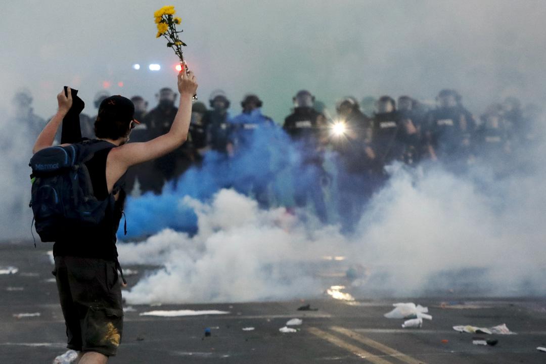 2020年5月30日,美國明尼蘇達州阿波利斯市,示威者手執鮮花站在防暴警察前。