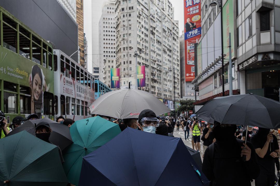 2020年5月24日,市民在香港島一帶發起反對國安法及國歌法遊行,示威者打開雨傘作防線。