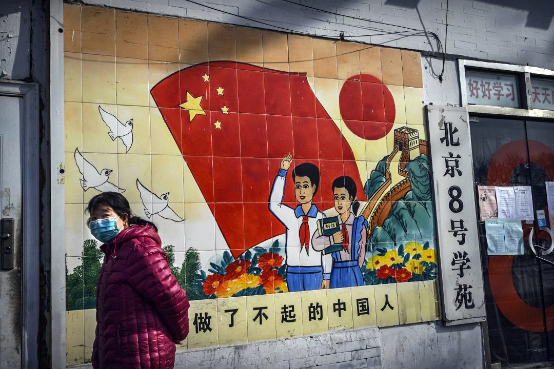 2020年2月8日北京,一名中國婦女戴著口罩在北京的宣傳壁畫走過。 攝:Kevin Frayer/Getty Images