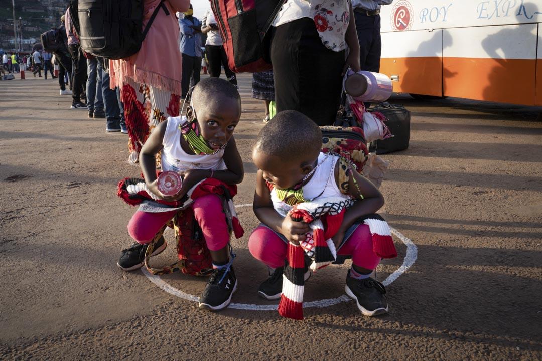 2020年5月4日,非洲盧旺達的小孩站在白色圈子裡排隊等巴士。 攝:Simon Wohlfahrt/AFP via Getty Images