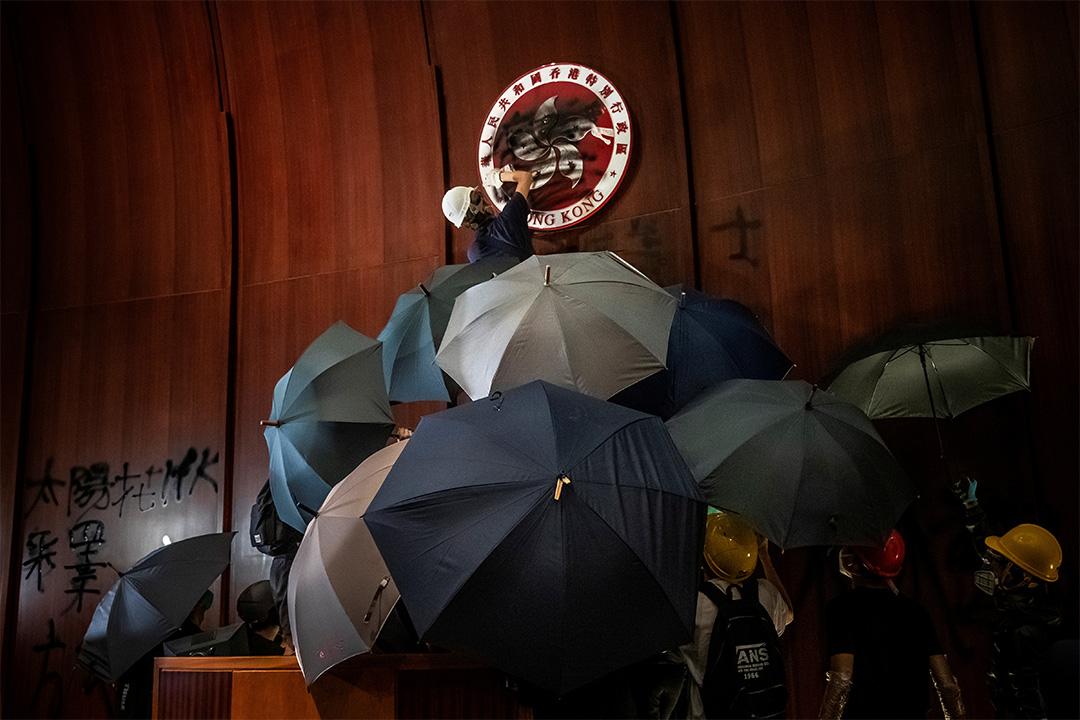 2019年7月1日香港,示威者佔領立法會,一名男子在香港區徽上噴漆。