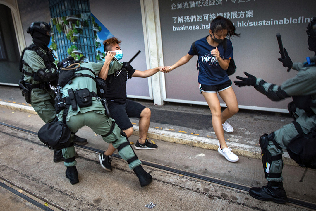 2019年10月5日,一對戴著口罩的示威者在遊行結束後,突然遭防暴警察追捕。