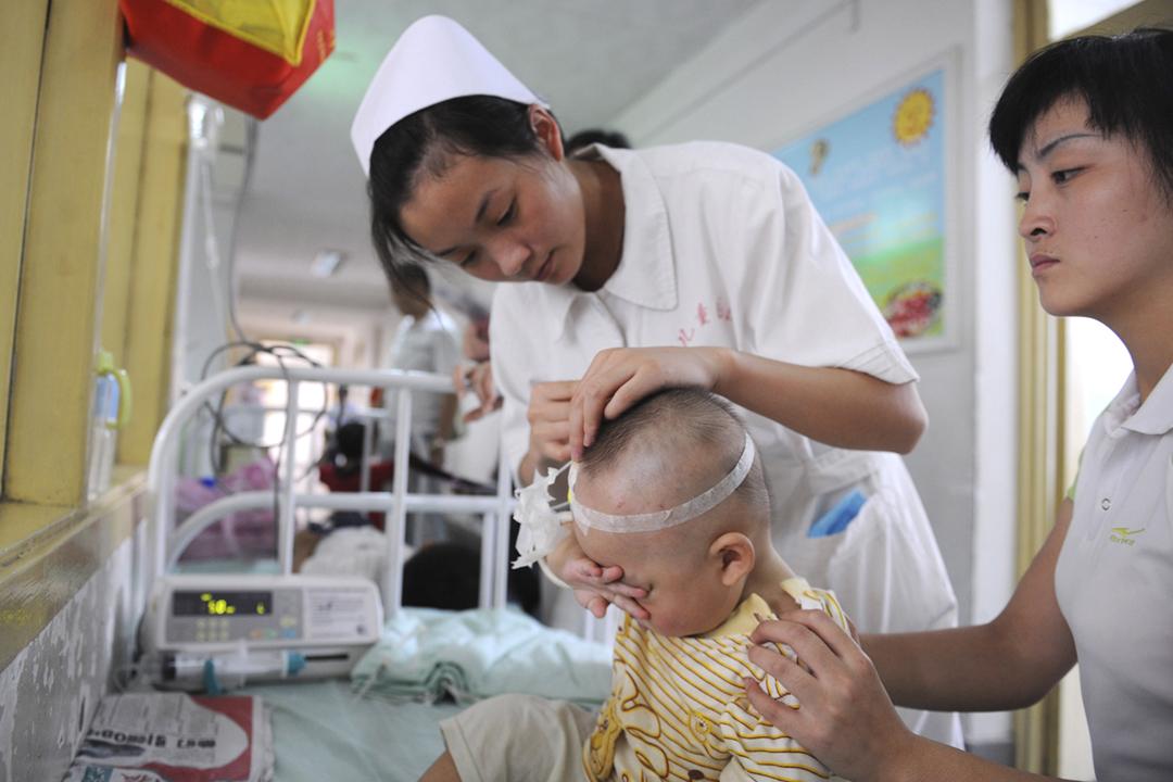 中國乳製品品質及安全、生產及銷售、當局監督機制等,多年來備受關注。2008年,三鹿集團所生產的奶粉被揭發添加化工原料三聚氰胺及三聚氰酸,導致數以萬計嬰幼童患上腎結石等病症;圖為當年9月22日在成都市兒童醫院,一位護士正為病童作護理治療。 圖片來源:China Photos / Getty Images