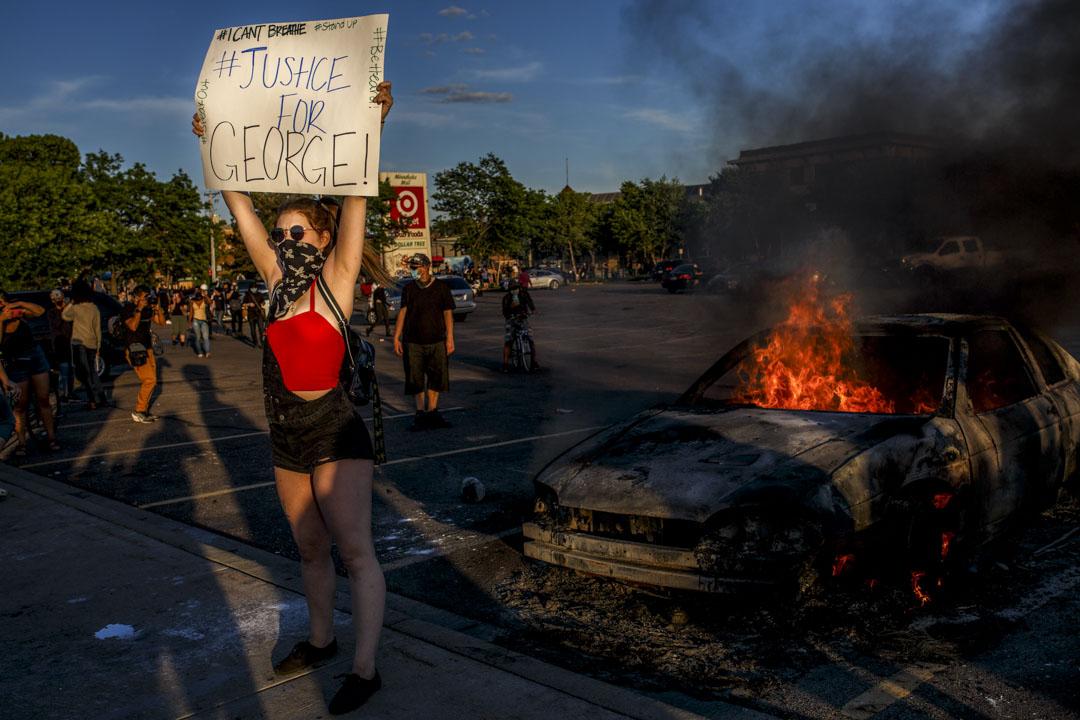2020年5月28日美國明尼蘇達州阿波利斯市,示威者於商店外示威者舉起「Justice for George」的牌子。