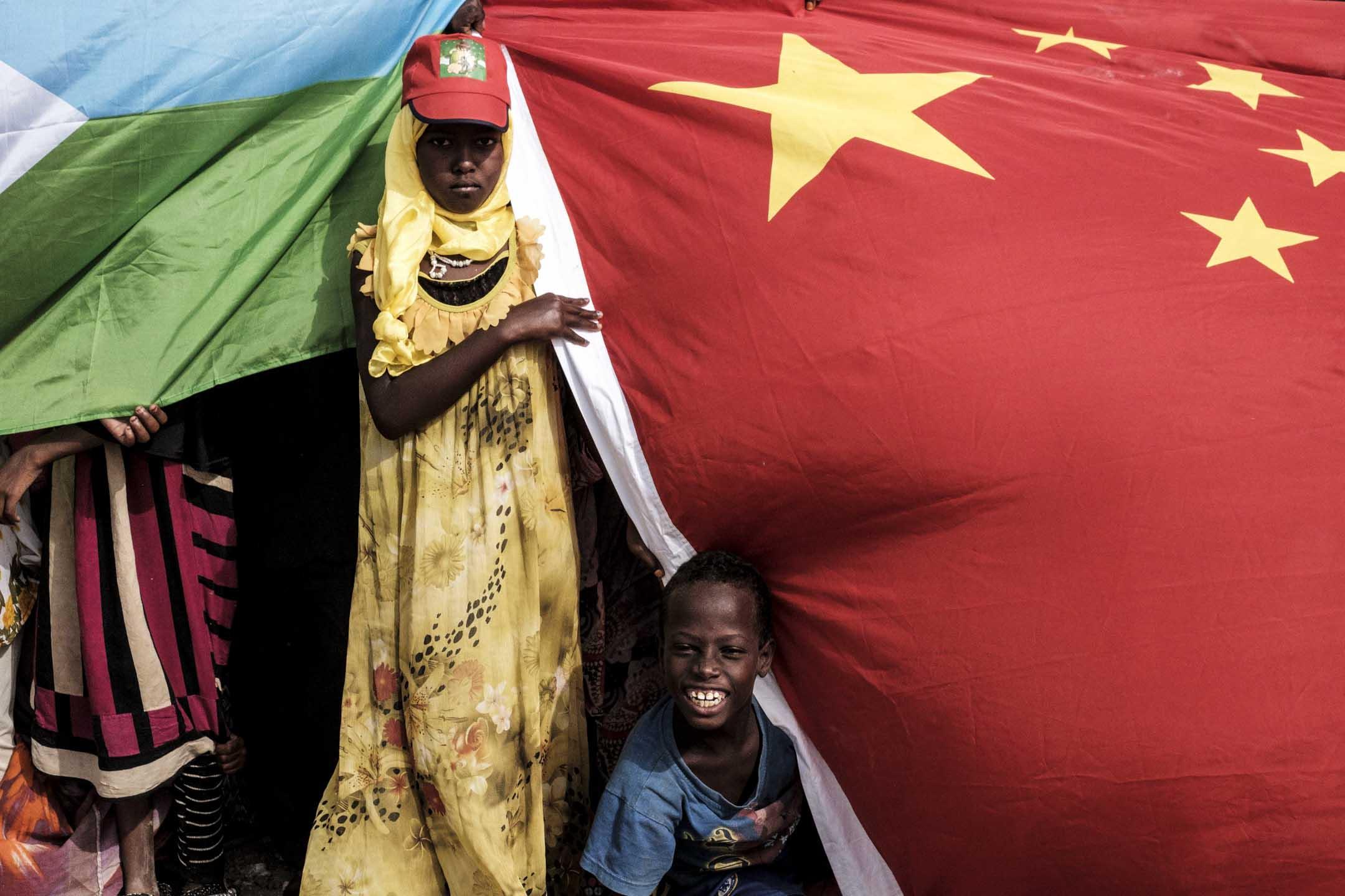 2018年7月4日,非洲吉布一個新的住房建設項目啟動儀式上,懸掛著中國和吉布提國旗。 攝:Yasuyoshi Chiba/AFP via Getty Images
