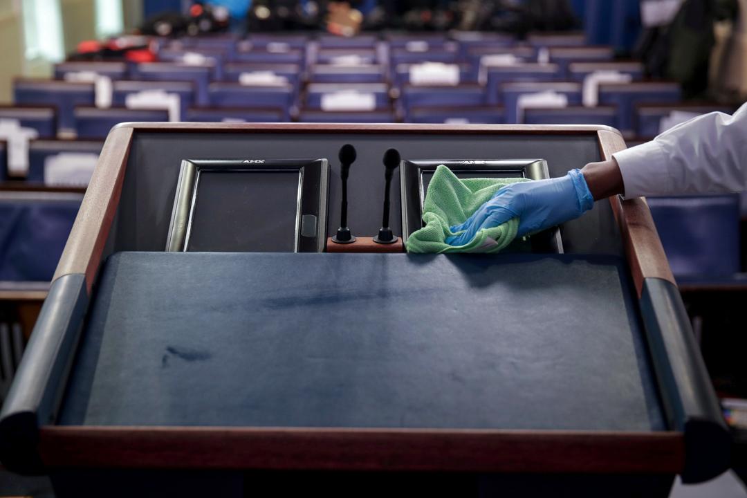 2020年3月23日,每日疫情簡報會開始前,清潔工正在消毒白宮新聞簡報室的講台。