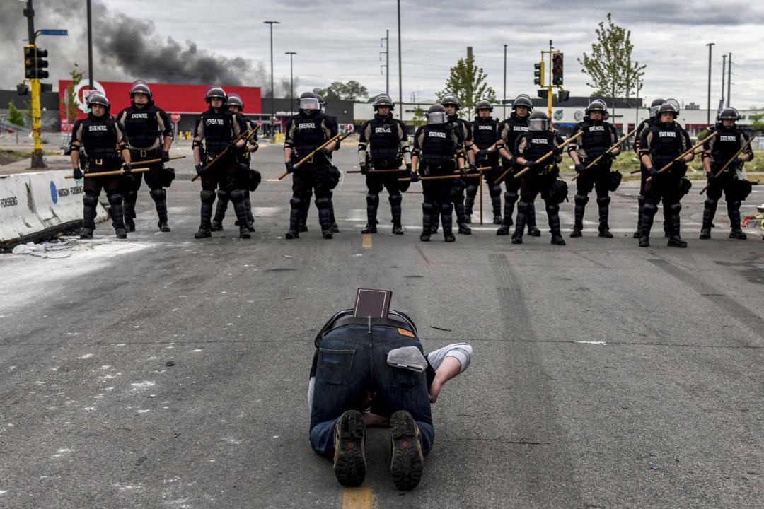 2020年5月29日美國明尼蘇達州阿波利斯市,一名被拒絕通過封鎖區的居民跪在地上於警察前哭泣。