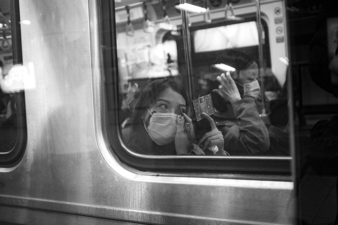 2020年4月13日台北,一名女士在車廂內化妝。