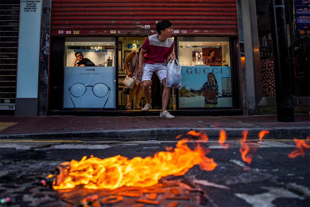 2019年11月2日香港,示威者與防暴警察發生衝突,一名顧客謹慎地離開了眼鏡店。