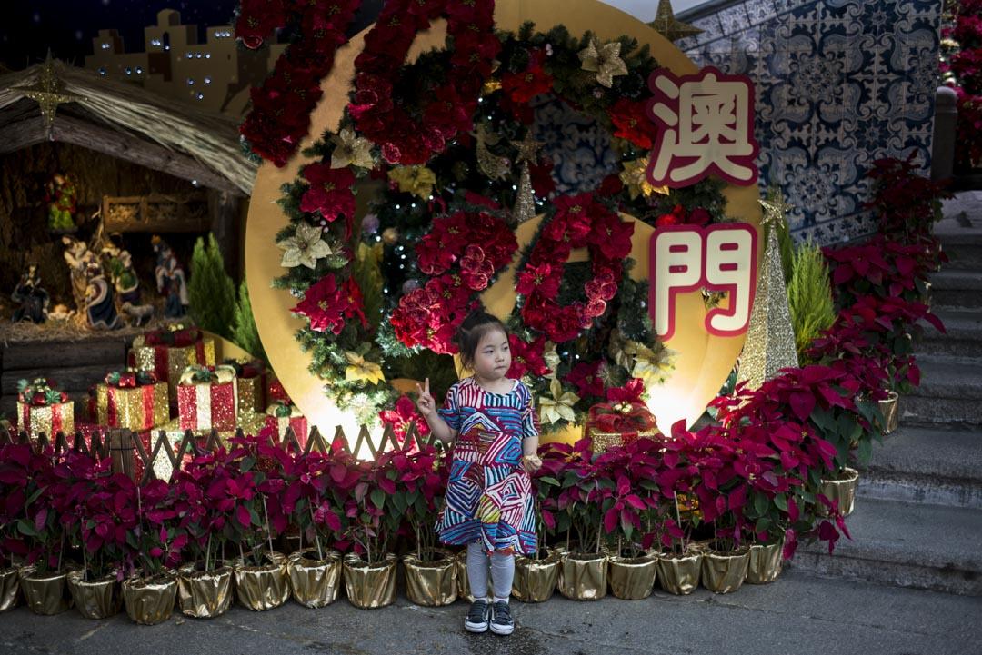2019年12月,女孩在一個澳門回歸紀念展上展示勝利手勢。