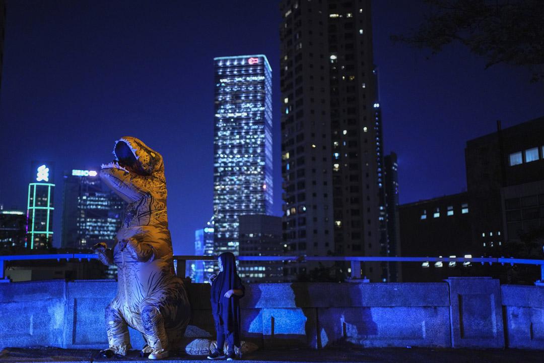 2019年10月31日,反對政府禁蒙面法的示威者裝扮成恐龍。 攝:Vincent Yu/AP/ 達志影像