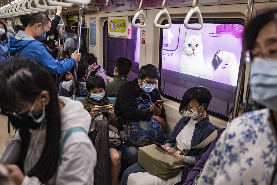 2020年4月13日台北,乘客在捷運上看手機。 攝:陳焯煇/端傳媒