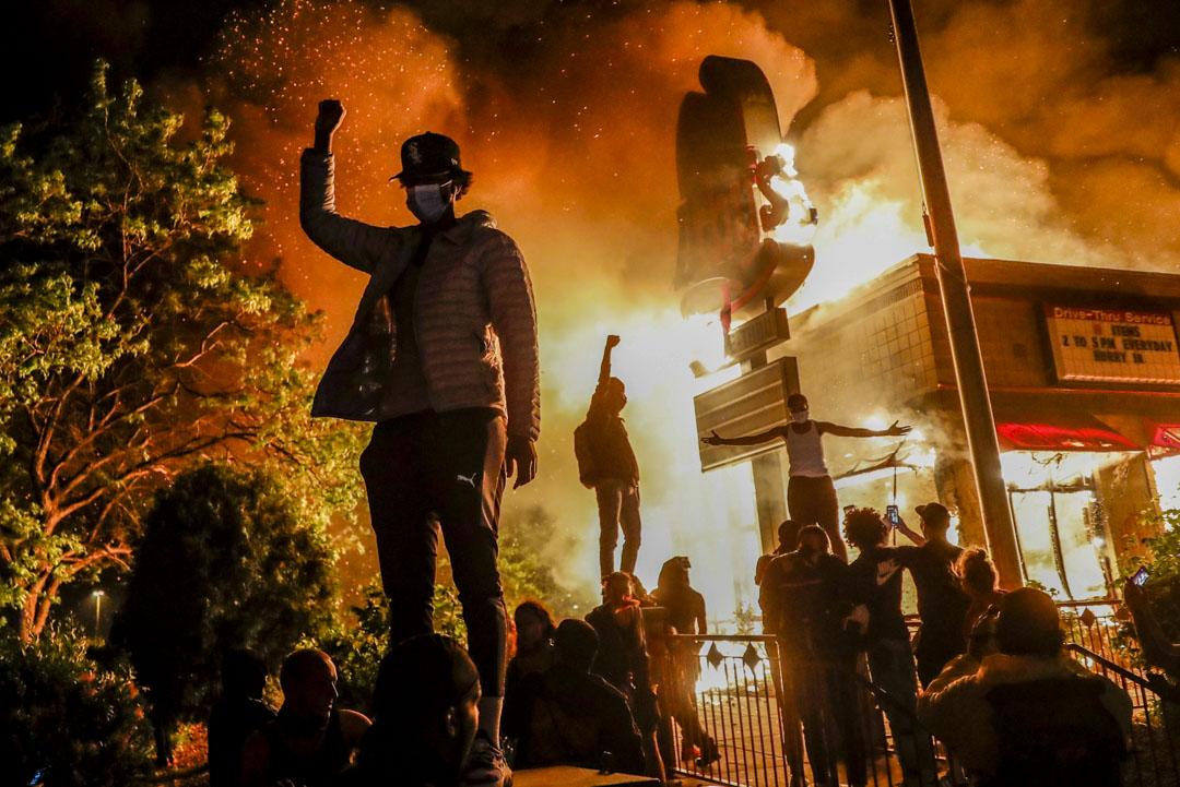 2020年5月29日,美國明尼蘇達州阿波利斯市一位示威者在焚燒中的快餐店外示威。數天前美國黑人喬治·佛洛伊德(George Floyd)在美國中西部明尼蘇達州的明尼阿波利斯市(Minneapolis)被白人警官用膝蓋壓制頸部8分鐘,弗洛伊德其後身亡。觸發了美國近年來圍繞種族問題的最大規模抗議浪潮。。 攝:John Minchillo/AP/達志影像