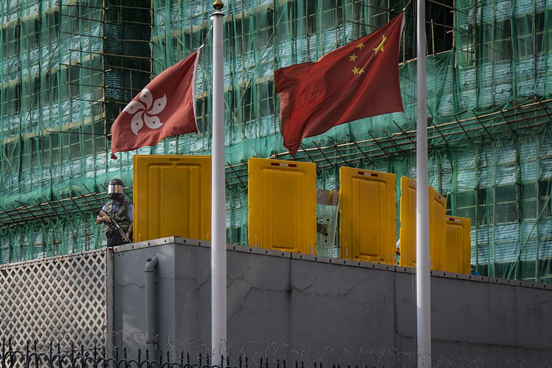 2019年8月12日,深水埗警署的警察在警署內觀看警署外的示威者。 攝:陳焯煇/端傳媒