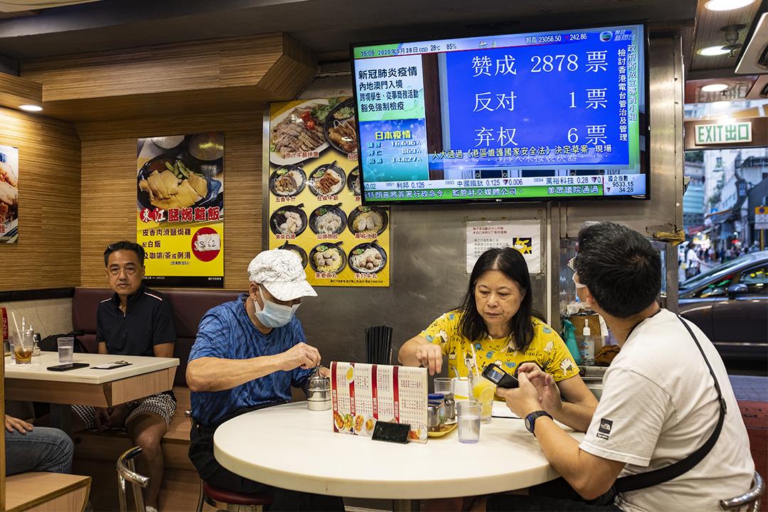 第十三屆全國人大今日下午(5月28日)閉幕,以2878票贊成、1票反對、6票棄權表決通過「港區國安法」決定草案,確定將列入《基本法》附件三,由港府公布實施。 圖爲2020年5月28日香港茶餐廳,電視上正播放人大表決新聞。
