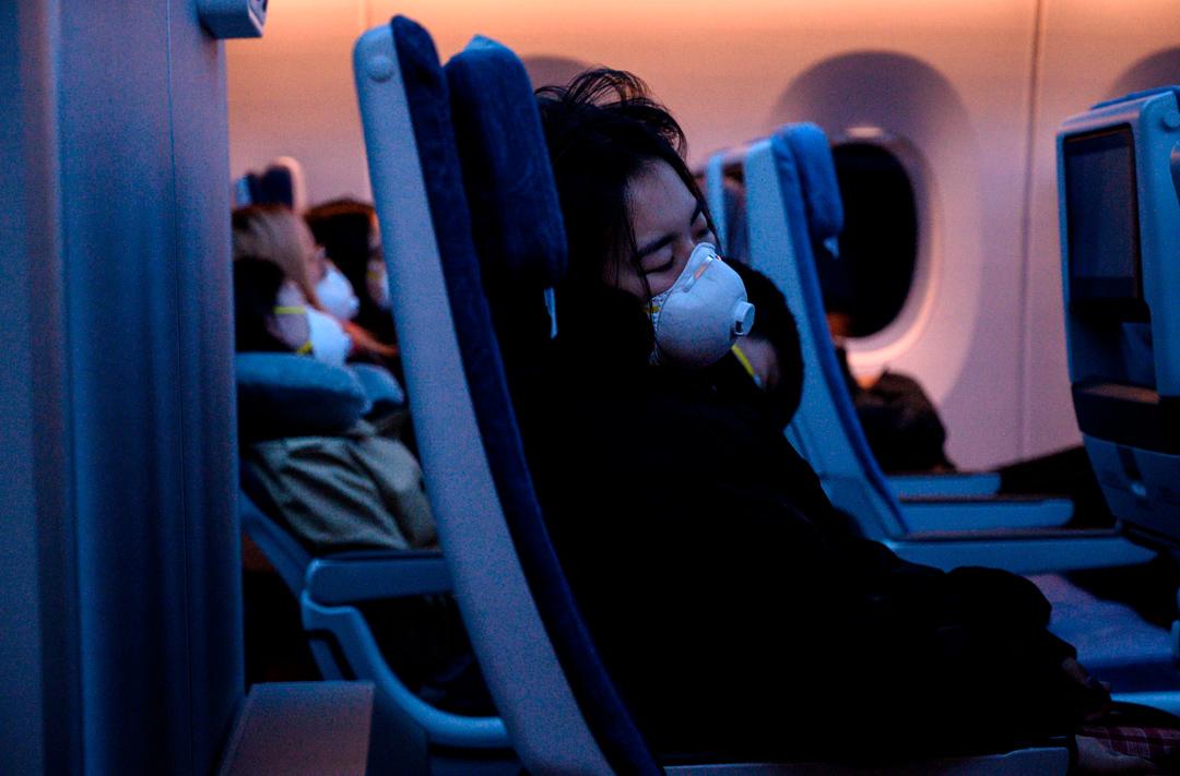 2020年2月4日,飛往上海的客機上的一名乘客戴著口罩。