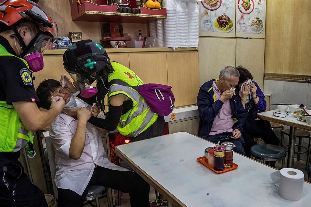 2019年11月2日,一名防暴警察在開槍催淚彈以驅散反政府示威者,一名餐館員工得到志願者的護理。