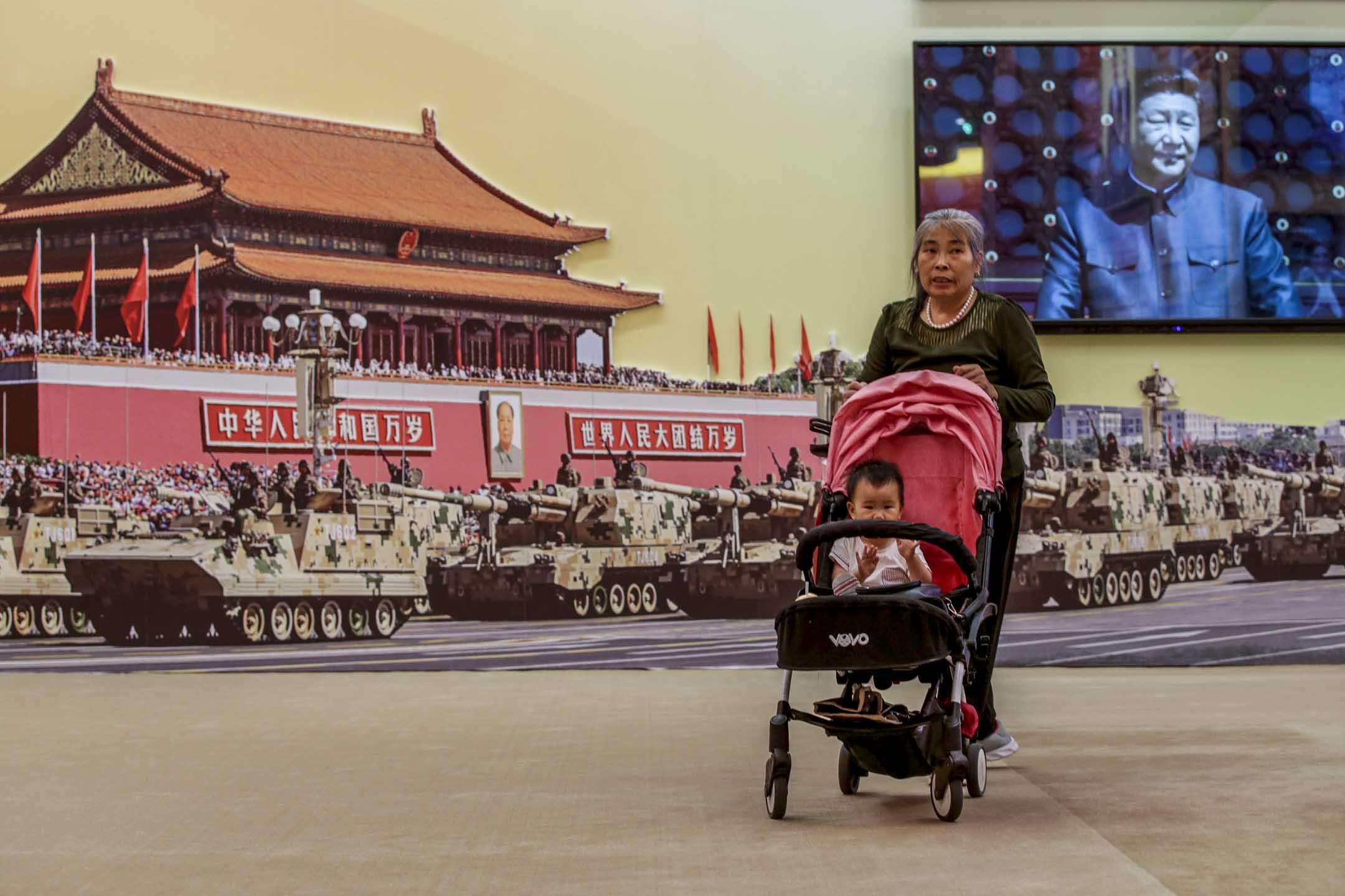 2019年9月24日,一位婦人推著孩子參觀國慶70周年展覽,後面屏幕播放著國家主席習近平主持的閱兵儀式。 攝:Jason Lee/Reuters/達志影像