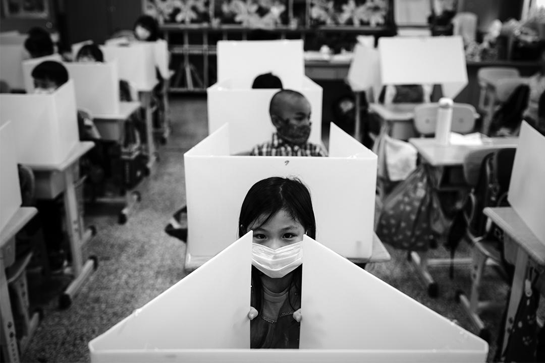 2020年2月26日松山,台灣中小學已開學,一所國小的學生在中午午餐時間,學生拿起膠板分隔彼此,以防止飛沫傳染。