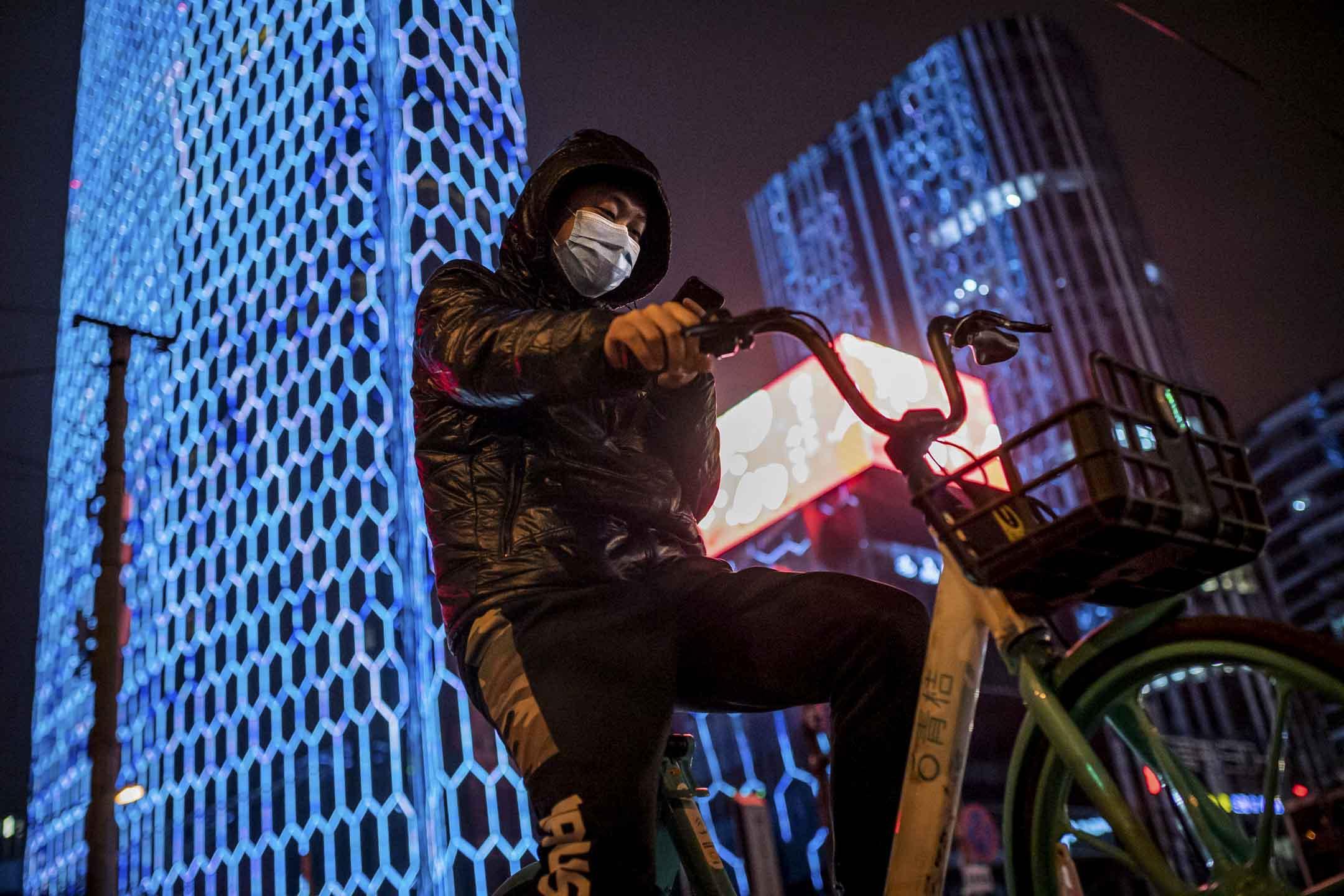 2020年2月24日,北京一名戴著口罩的男子在踏單車。 攝:Nicolas Asfouri/AFP via Getty Images