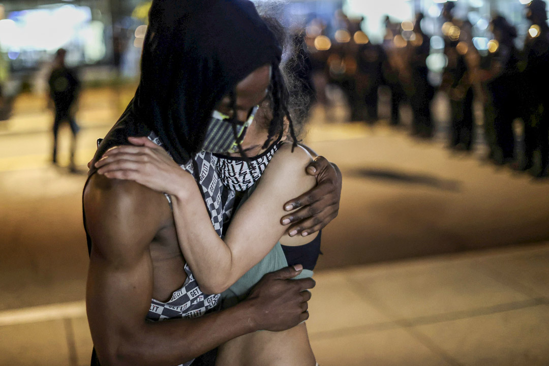 2020年5月30日,示威者在美國白宮附近的警察防線前擁抱。