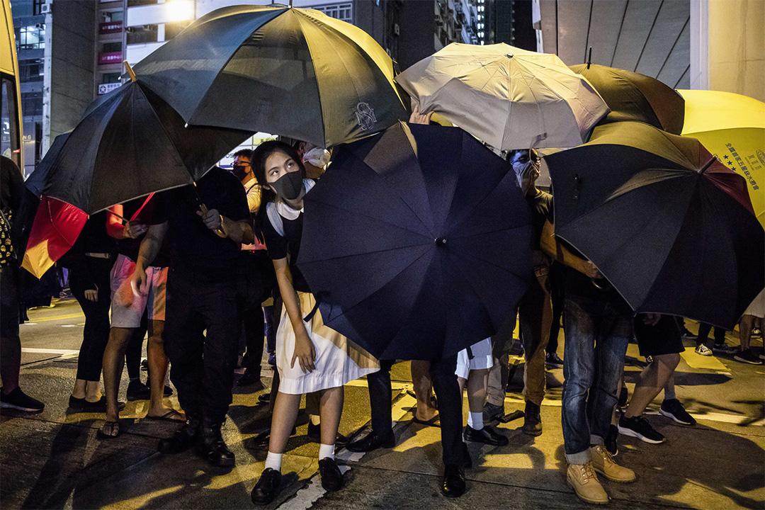 2019年9月3日,一名穿著校服的示威者在太子警署門外示威,在雨傘陣內向外眺望。