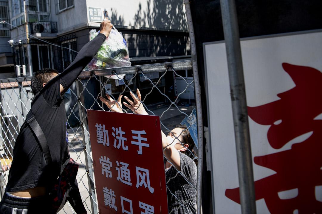 2020年6月14日北京,在封閉的新發地市場附近發生了2019冠狀病毒爆發後,送貨員將一包貨物交給正在封鎖的住宅區客戶。