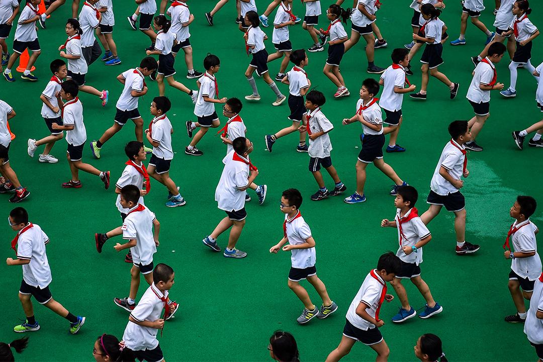 2017年9月27日上海,學生們在學校的體育課期間在操場上奔跑。 攝:Chandan Khanna/AFP via Getty Images