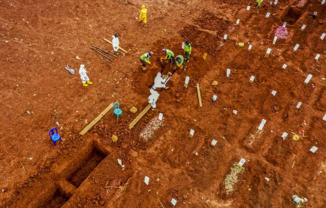 2020年4月15日,工人將新冠狀病毒受死者的棺材放在雅加達某公墓的墓地中。 攝:Bagus Saragih/AFP via Getty Images