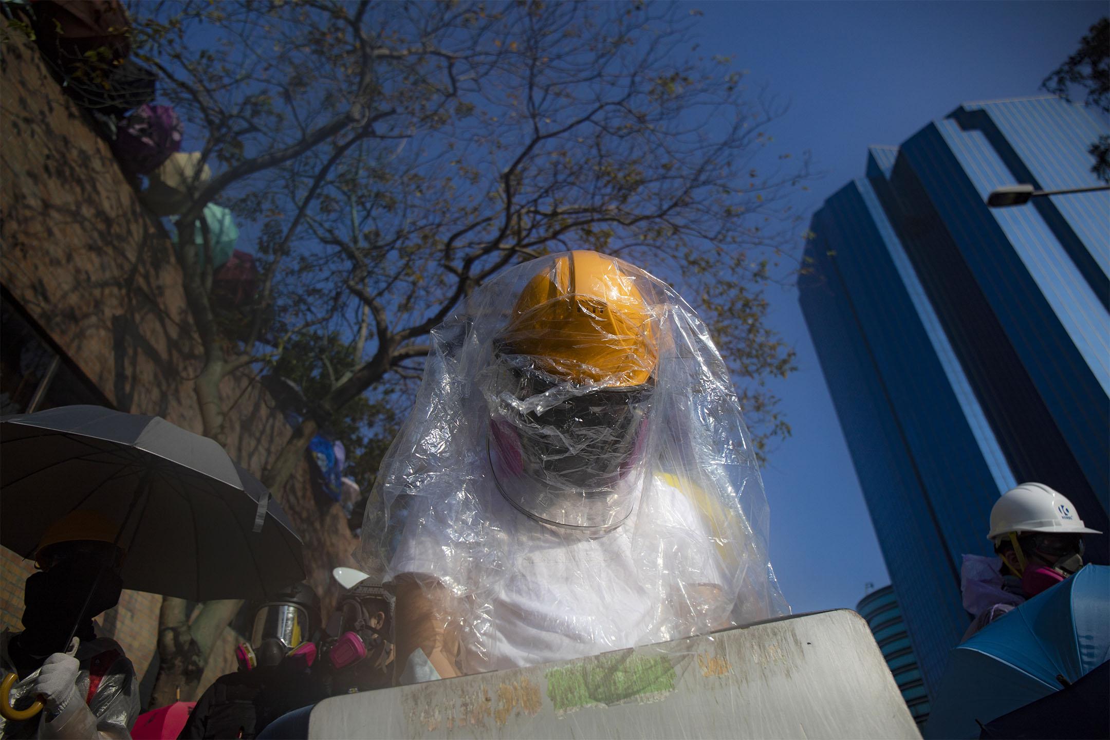 2019年11月17日香港,示威者佔領香港理工大學,警察以水砲車驅散,一名示威者穿上雨衣。 攝:陳焯煇/端傳媒