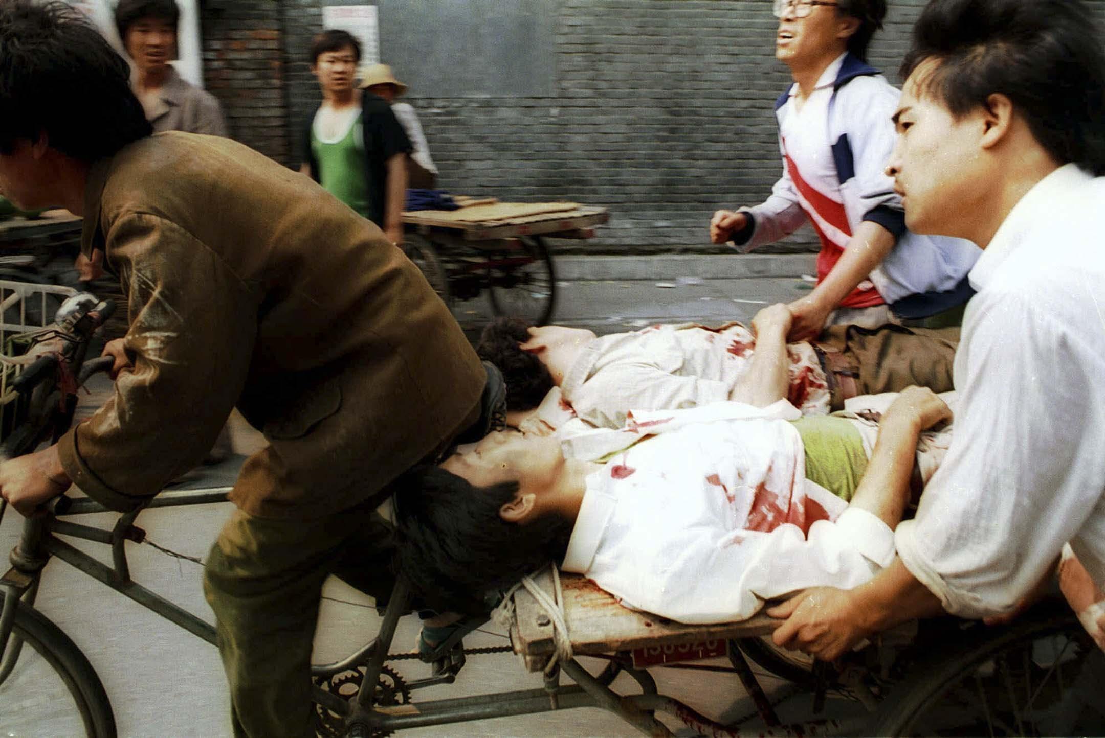 1989年6月4日,人力車司機在旁人的幫助下,將天安門廣場的傷者運送往醫院。 攝:Liu Heung Shing/AP/達志影像
