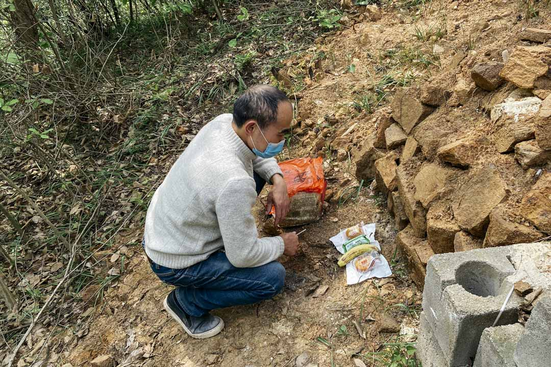 鄢小文在大兒子鄢成的墓地前拜祭。