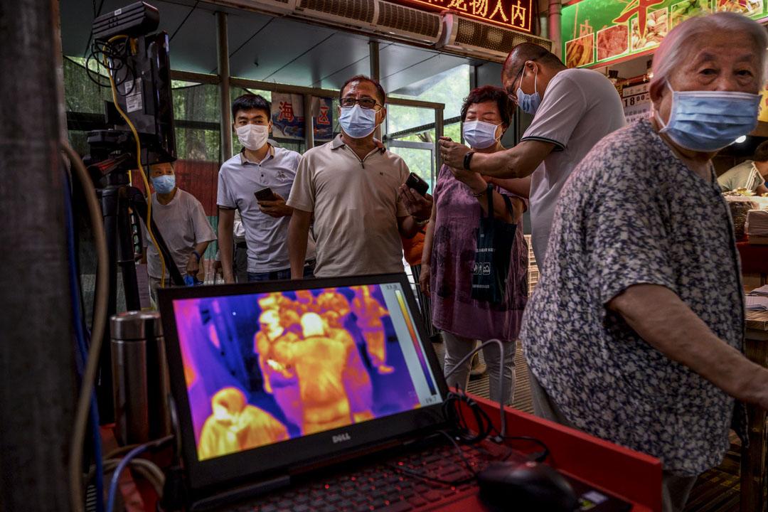 2020年6月19日北京一個地方市場的入口,顧客接受體温檢查。