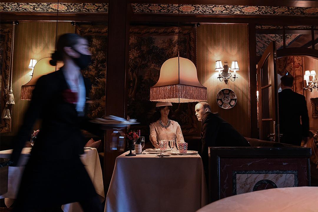 2020年5月29日華盛頓市華盛頓旅館的餐廳,女服務員戴上口罩在重新開業的第一天經過餐廳內的人偶。