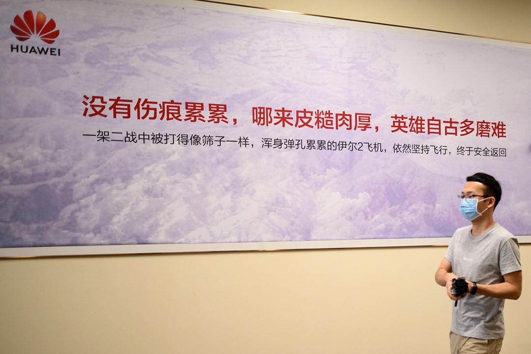 2020年5月18日在華為位於中國深圳市的總部,一名華為員工經過公司設置的一幅宣傳標語。 攝:Noel Celis / AFP via Getty Images
