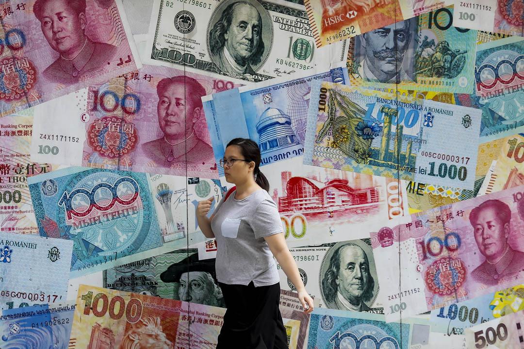 一名女士在香港中環的一家貨幣兌換店前走過。 攝:Kin Cheung/AP/達志影像