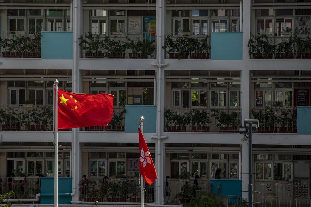 圖為2020年6月29日,香港一間學校所懸掛的中國國旗及香港特區區旗。 攝:Paul Yeung / Bloomberg via Getty Images