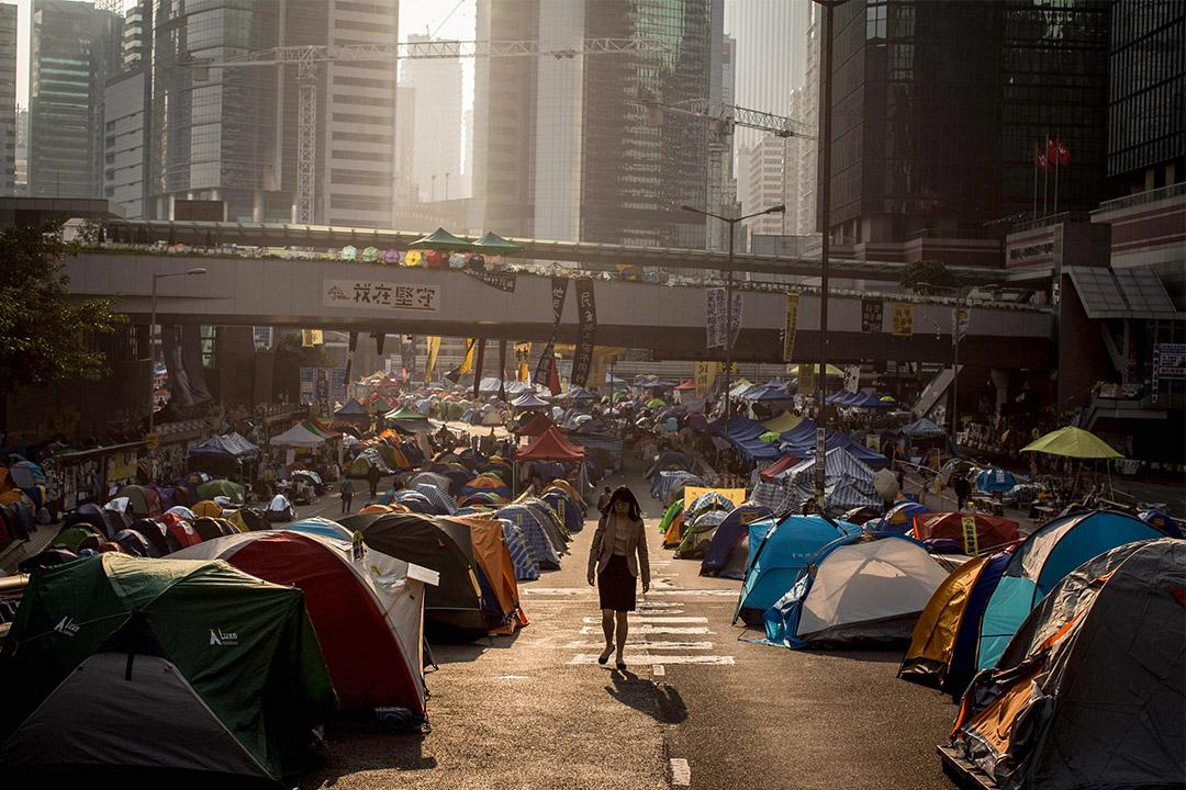 2014年11月18日香港金鐘,一個女人走在金鐘示威者佔領的馬路上。  攝:Chris McGrath/Getty Images