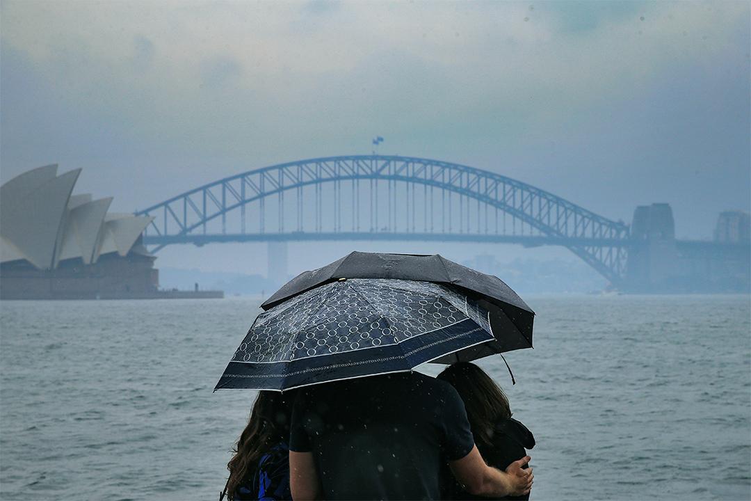 2020年1月17日澳洲悉尼,遊人在雨中看悉尼海港大橋。 攝:Jenny Evans/Getty Images