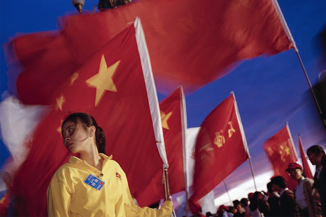 1999年10月1日,中華人民共和國建國50週年慶典上,觀眾和參與者在天安門廣場上閒逛。