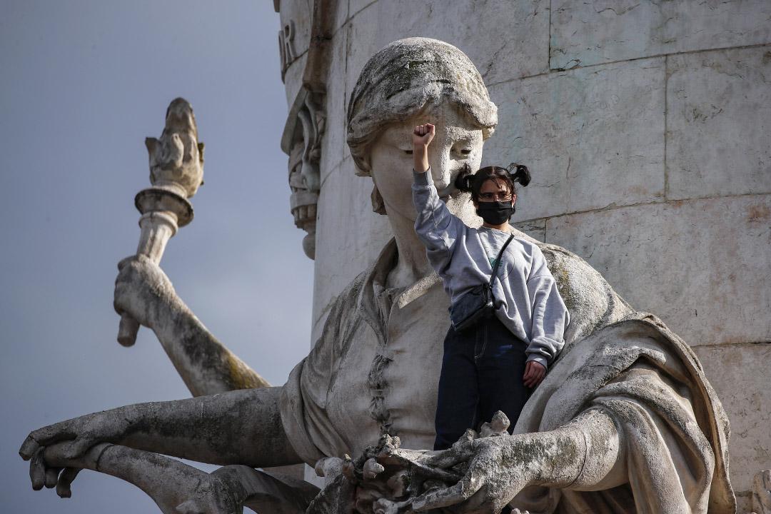 2020年6月9日,巴黎舉行的反對種族主義集會上,一名示威者緊握拳頭站在共和廣場的雕像上。 攝:Francois Mori/AP/達志影像