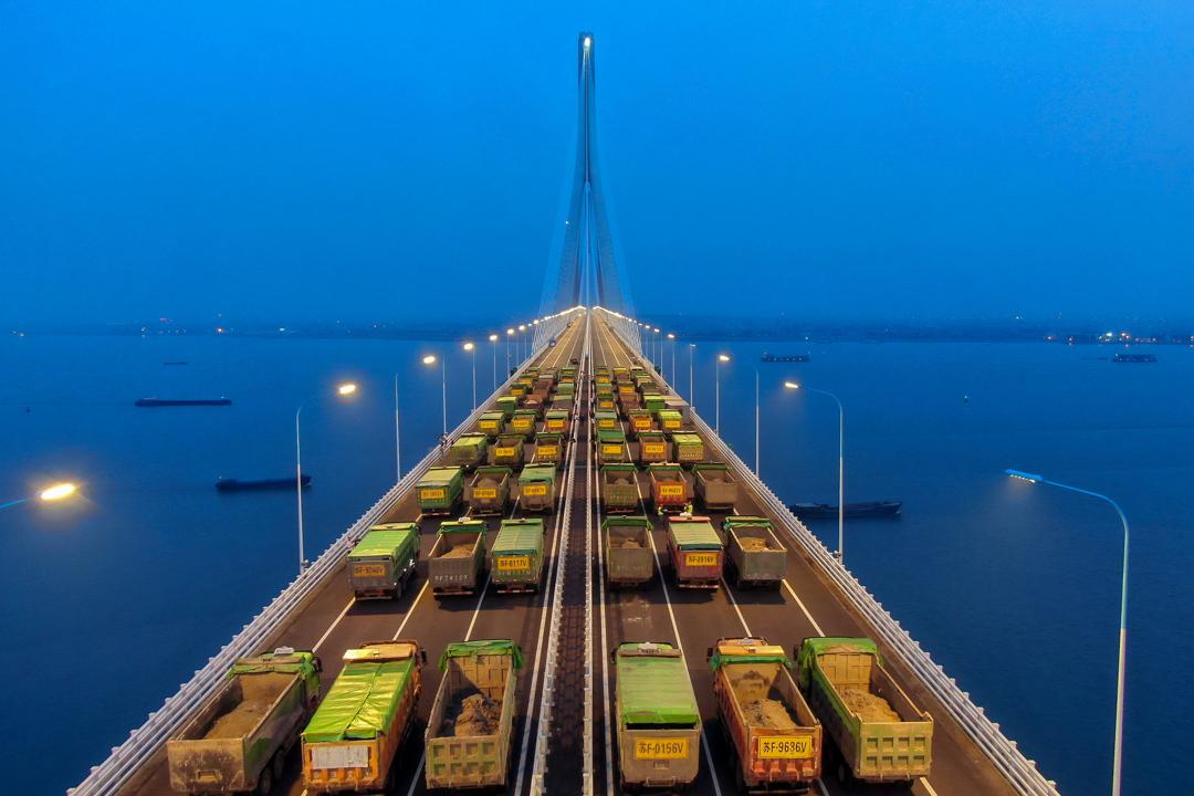 2020年5月27日,江蘇省的蘇通長江公路大橋上駛滿貨車。 攝:STR/AFP via Getty Images