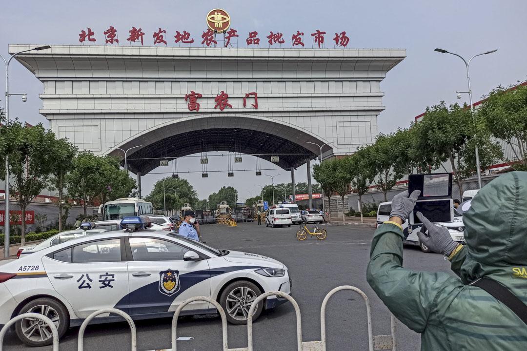 2020年6月13日北京,警察守衛在封鎖的新發地市場的入口。