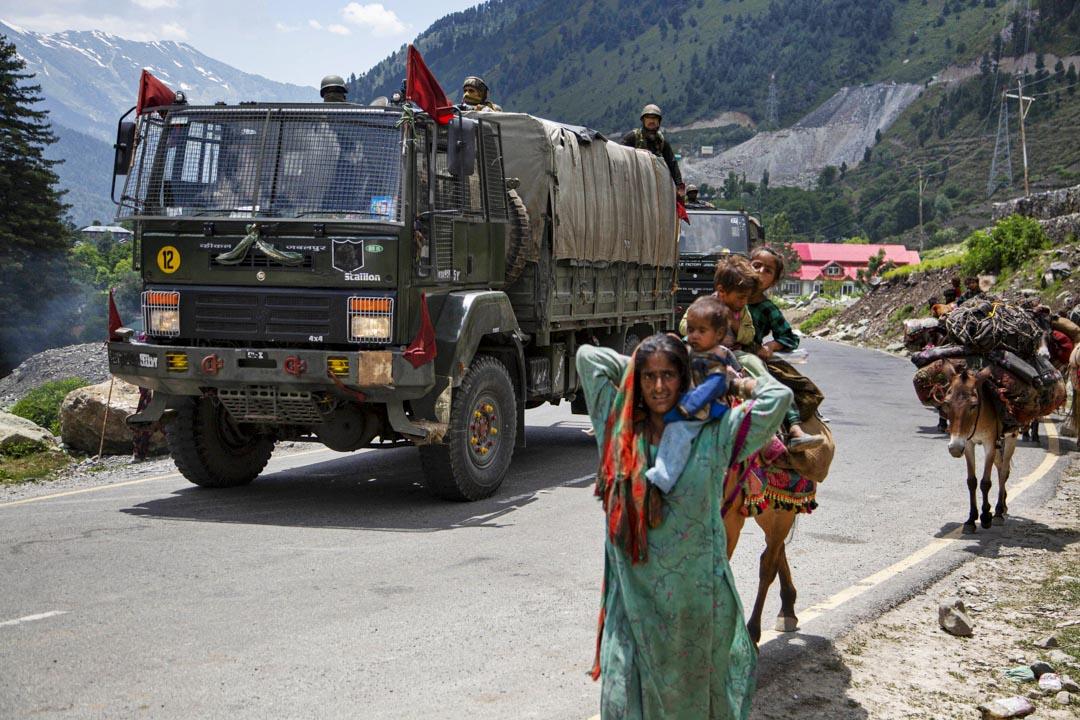 2020年6月17日,印度軍隊在印度斯利那加東北部的高速公路上行駛時,克什米爾人在路上行走。 攝:Mukhtar Khan/AP/達志影像