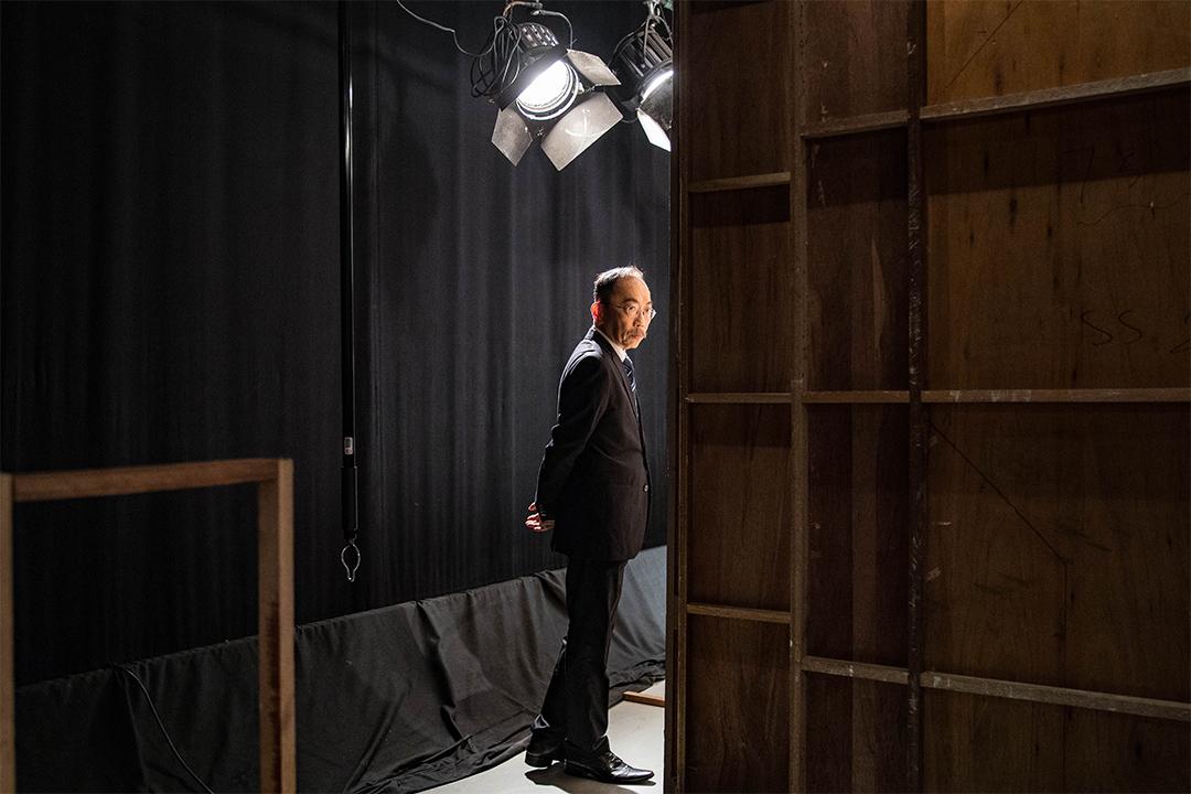 扮演校長的吳志森在拍攝期間等待進入教室場景。 攝:陳焯煇/端傳媒