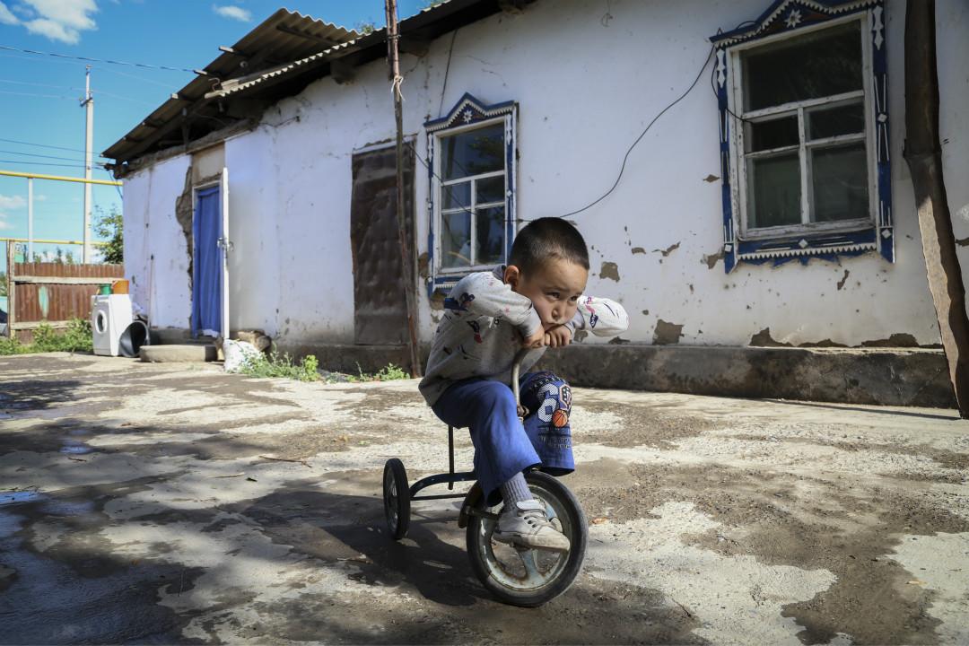 2020年6月13日,阿里夫·巴克塔利(Alif Baqytali)在哈薩克斯坦春賈(Shonzhy)家中騎三輪車。他的母親是美聯社採訪者古麗娜爾·奧米爾扎克(Gulnar Omirzakh)。 攝:Mukhit Toktassyn/AP Photo