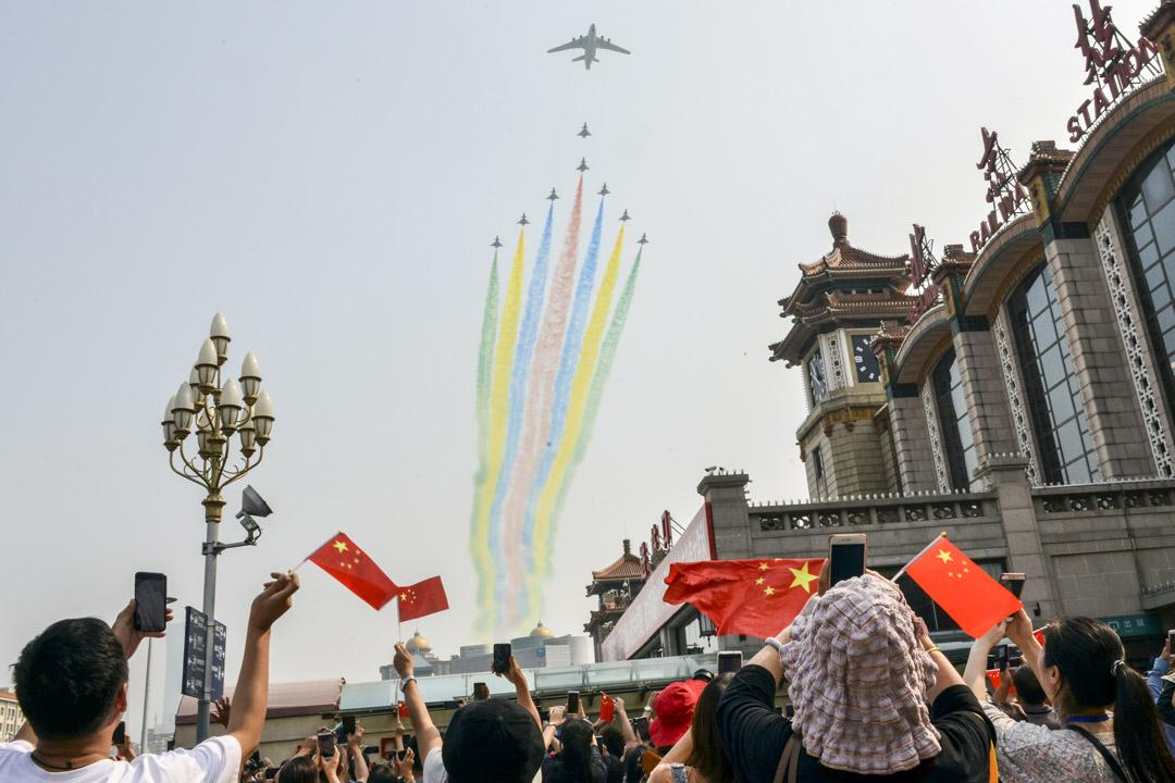 2019年10月1日,北京正在舉行中華人民共和國成立七十周年的閱兵典禮,民眾在北京站外觀看。