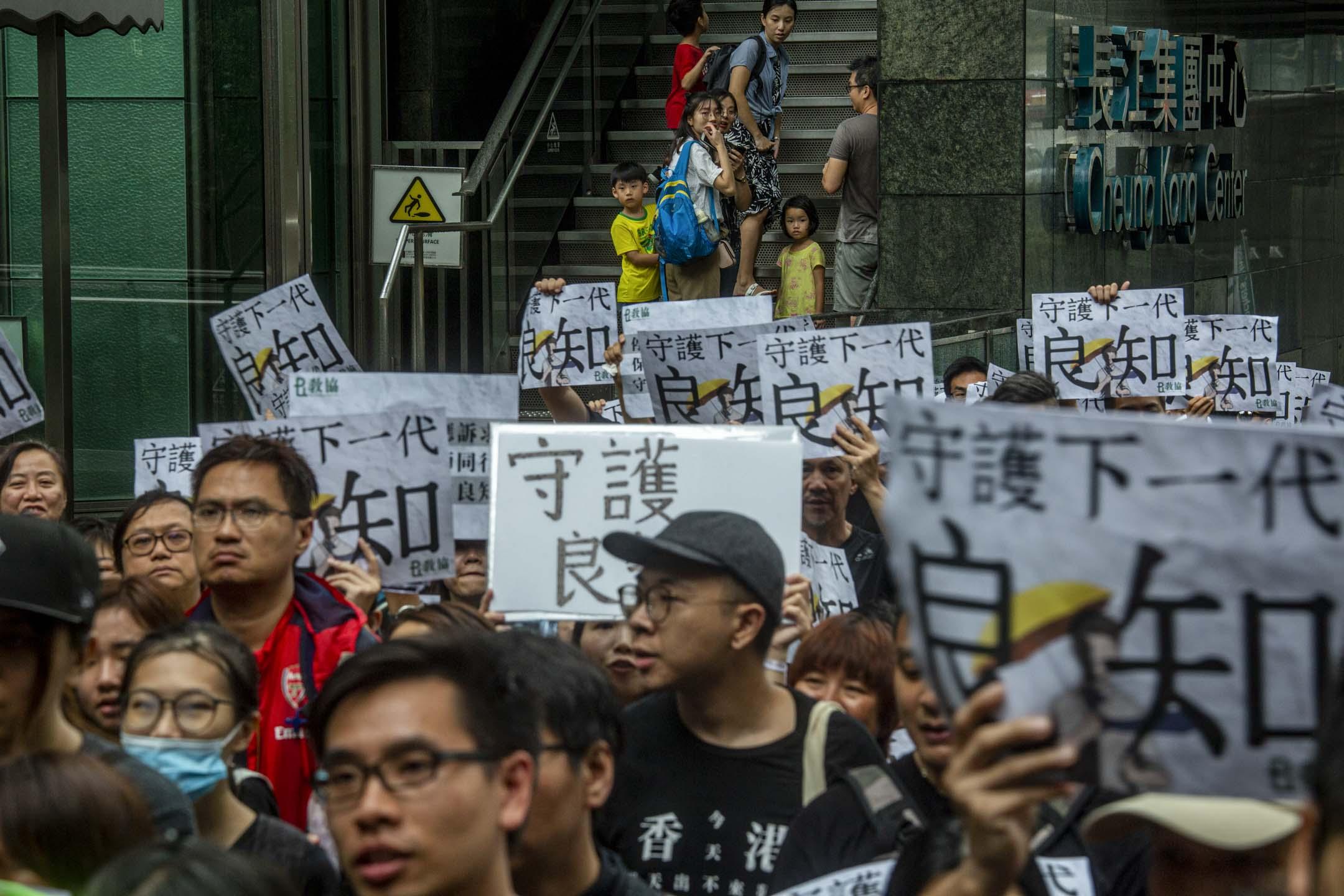 2019年8月17日,有教師發起「守護下一代,為良知發聲」的遊行,期間大雨滂沱,參加者身上貼上「我是香港教師」的貼紙,又手持「守護下一代 良知」、「憑老師守護」的標語。  攝:林振東/端傳媒