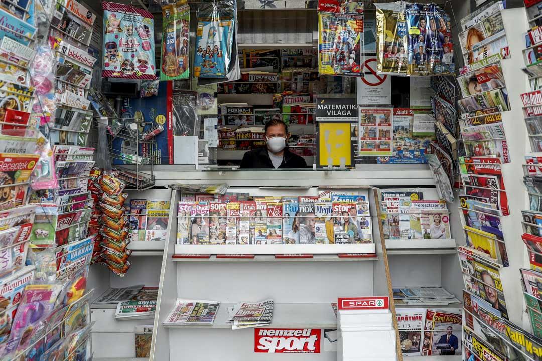 2020年3月30日匈牙利首都布達佩斯,戴著防護口罩的商販在報攤裡等待顧客。