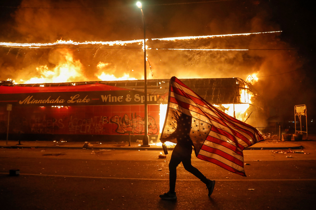 2020年5月28日,美國明尼亞波利斯的示威者在一家起火的商店外拿著倒掛的美國旗。